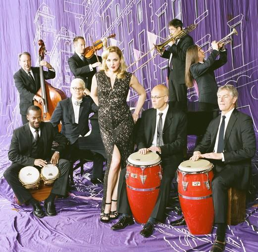 "Pink Martini, the ""little orchestra"" with a wide-ranging repertoire of classy arrangements of vintage songs in several languages. Vocalist Storm Large, center; founder Thomas Lauderdale is seated at the piano to her right."