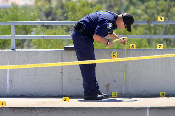 A Newport Beach police crime scene investigator takes notes Monday along the eastbound side of Pacific Coast Highway. A woman's body was found nearby Monday morning.