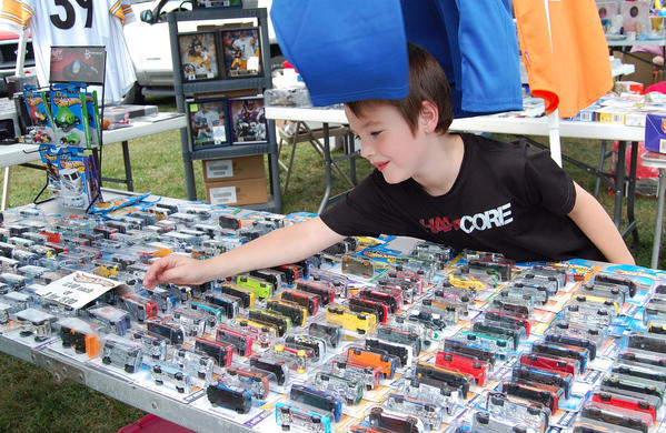 Jacob Wood, 6, of Fayetteville, Pa., checks out toy cars at the Quincy (Pa.) Ox Roast's community yard sale Monday.