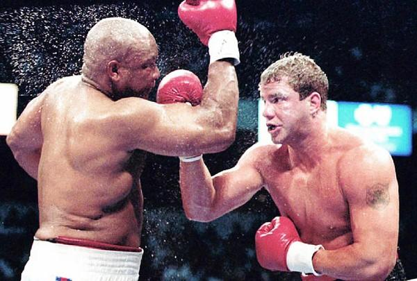 George Foreman, left, and Tommy Morrison battle in the World Boxing Organization heavyweight title in June 1993, which Morrison won in 12 rounds.