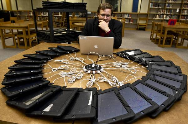 Eric Cooprider, the director of IT Services and network administration for Isle of Wight County Schools, clears iPads that were used last year for the new school year.