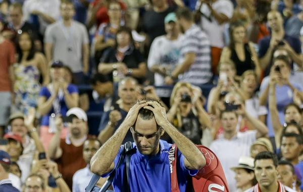 Roger Federer walks off the court after losing to Tommy Robredo in a fourth-round upset at the U.S. Open on Monday.