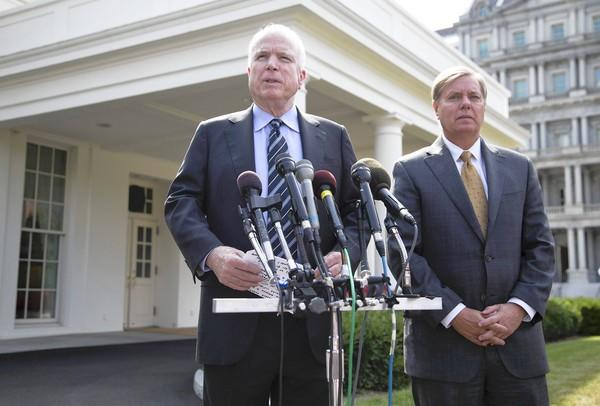 Sens. John McCain (R-Ariz.), left, and Lindsey Graham (R-S.C.) speak with reporters outside the White House. The two Republican hawks may prove pivotal to President Obama's efforts to secure congressional approval for airstrikes in Syria.