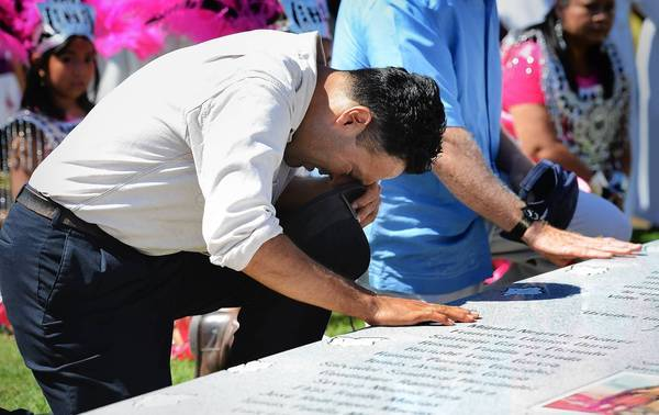 Musician Lance Canales bows his head at a memorial at Holy Cross Cemetery. The stone is inscribed with the names of the 28 farmworkers who died in a 1948 plane crash.