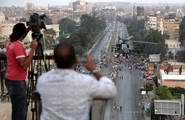 Journalists film an Egyptian military helicopter as it flies by the presidential palace in Cairo on July 5, 2013.