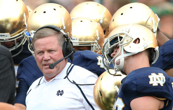 Notre Dame coach Brian Kelly huddles with his team during a game against Temple at Notre Dame Stadium Saturday.