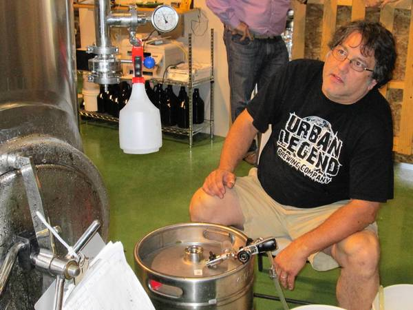 Tim Hoerman, an owner of the new Urban Legend Brewing Company, transfers beer from a vat to a keg for drinking.