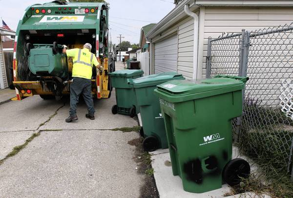 A Waste Management employee collects trash in Berwyn in 2011. The company announced it would deliver new garabage carts to Orland Park residents in September as part of a 10-year waste removal contract the village signed earlier this summer.
