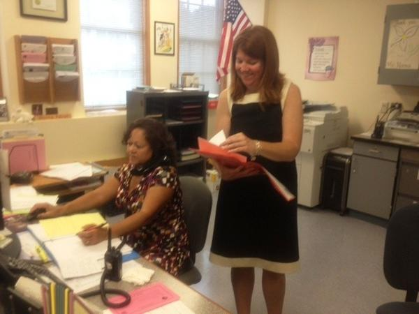 Principal Sarah Harris, right, reviews paperwork after opening day of classes at Vance Village School in New Britain.