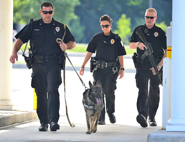 Hagerstown Police Department officers, from left, Jason Batistig, Samantha Resse and Mitchell Filges, along with K-9 Fatima, comb the drive-thru lanes at Columbia Bank on Dual Highway on Tuesday. A Denny's restaurant employee was robbed Tuesday morning in the parking lot between the bank and restaurant.
