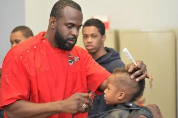 A student gets a haircut at Sunni Powell's Barber Shop in Englewood.