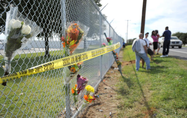 Police tape and flowers mark the site where two factory workers were fatally struck by an SUV while waiting at a bus stop on Race Street in Hanover Township, Lehigh County, last September. The driver of the SUV, Caitlyn Leigh Clark, 27, of Nazareth, is charged with vehicular homicide.