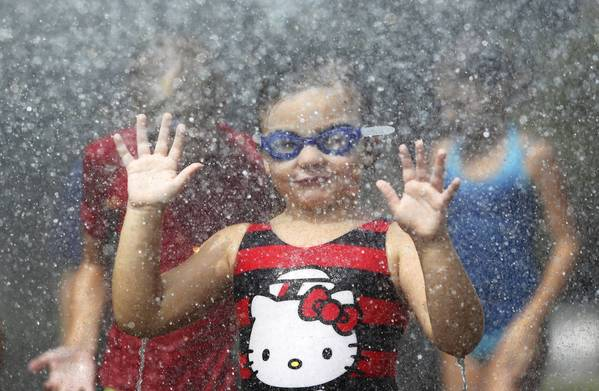"Kendall Carey, 5, plays under the spray from a fire hose provided by the Montverde Fire Dept., on Wednesday, August 14, 2013, during ""Water Day"" at the Helen Lehmann Memorial Library in Montverde."