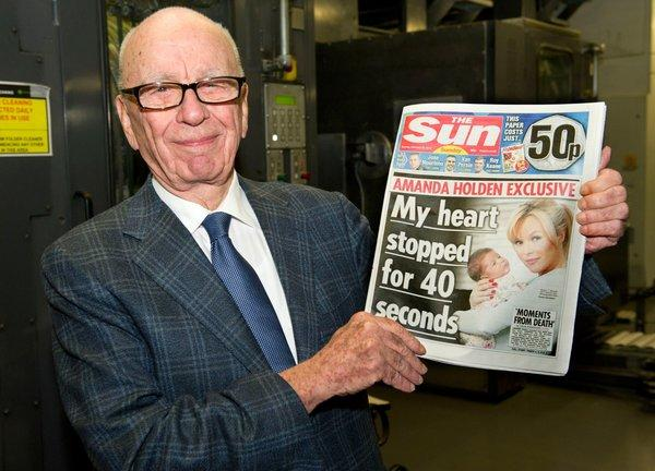 News Corp. on Tuesday sold its U.S.-based community newspaper group for an undisclosed price. Above, Rupert Murdoch, chairman and chief executive of News Corp., holds the first edition of British newspaper the Sun as it comes off the presses February 2012 in Broxbourne, England.