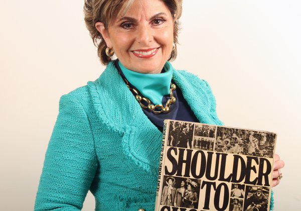 Los Angeles attorney Gloria Allred in her office with a book about women's suffrage by Midge Mackenzie.