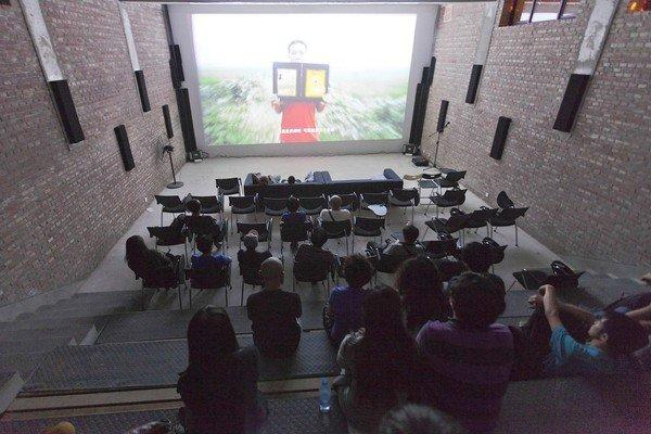 People watch a documentary film about Qian Yunhui, who died fighting for better compensation for seized land, at the Beijing Independent Film Festival in Beijing, China on Aug. 30, 2013. Chinese authorities, no fans of free-thinkers gathering in large numbers, have done their utmost each year to derail the decade-old fest.
