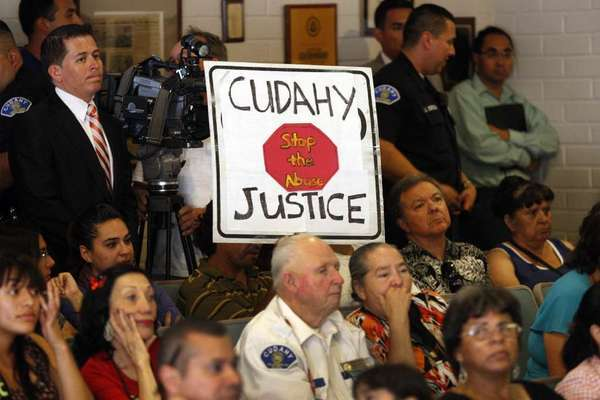 In July, a community activist holds a sign while listening to City Council members with other residents as they rally at City Hall to discuss the restoration of good governance to Cudahy.