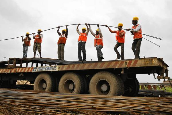 Workers unload iron rods from a truck in India, where officials hope new infrastructure projects will boost a sagging economy that once was flying high.