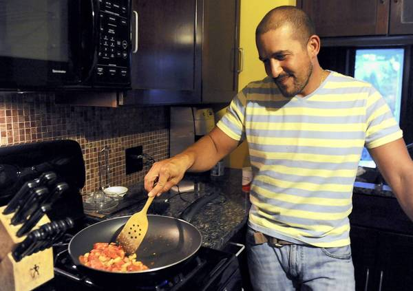 Joshua Attanasio, who volunteered to be a vegan for a month in advance of Bethlehem's VegFest, cooks dinner in his Bethlehem home.