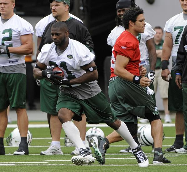 LaDainian Tomlinson takes a handoff from Mark Sanchez during New York Jets training camp back in 2010.