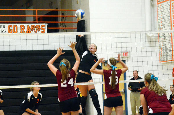 Harbor Springs Stephanie Sylvain (middle) goes up for an attack while Harbor Light Christians Sarah Bellmore (left) and Abby Johnson elevate for the block Tuesday at Harbor Springs High School.