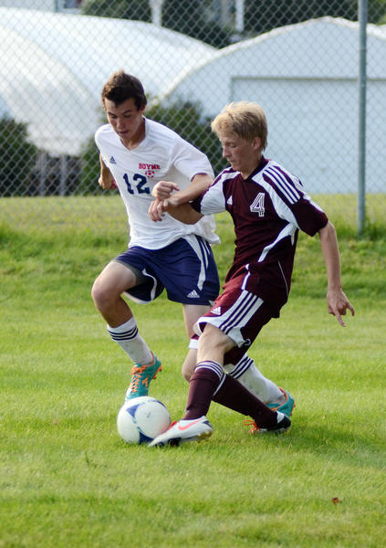 Charlevoix forward Brendan Britt (right) works the ball around Boyne City defender Trevor Day (left) during a Lake Michigan Conference match earlier this season.