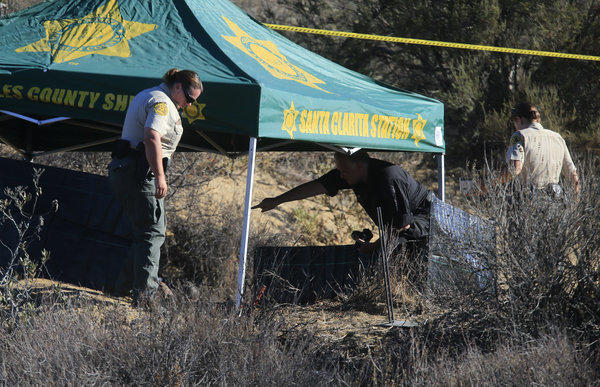 Investigators gather evidence at the scene off Lake Hughes Road near Castaic Lake where a burning body was discovered early Wednesday morning.