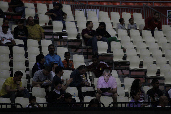 A fan looks at his laptop as he waits for play to resume at a World Cup qualifying basketball game during a power outage Tuesday in Caracas, Venezuela.