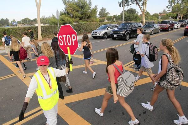 Crosswalk attendant Roberta Ray stops traffic along Eastbluff Drive as students make their way to Corona Del Mar High School during their first day back to school on Tuesday.