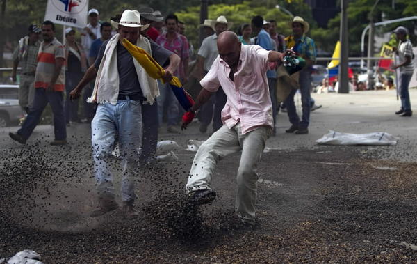 Farmers kick coffee beans during a march demanding government subsidies Aug. 20 in Medellin, Colombia.
