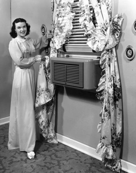 A woman dressed in a long nightgown pulls a ruffled floral print curtain back to show a modern air conditioner mounted in the window.
