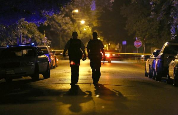 Chicago police officers investigate the scene of a shooting last week at 77th Street and Lowe Avenue.