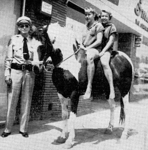 California Highway Patrol Officer Charles White grudgingly poses with Sharon McCartney and Charlene Freund (astride Apache) in early September 1953, after warning them that La Cañada's sidewalks were off limits to horseback riders.