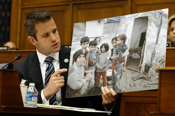Rep. Adam Kinzinger, a pilot and major in the Wisconsin Air National Guard, holds a photo of what he says are Syrian children as he addresses Secretary of State John Kerry at a House Foreign Affairs Committee hearing Wednesday in Washington.