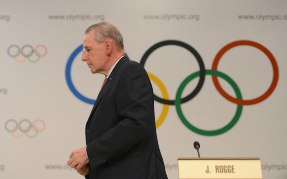 Jacques Rogge leaves his final press conference as IOC president. (Arne Dedert / EPA)