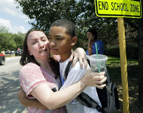 Lora Ross, left, hugs her son Jonathan Ross, 14, outside Spring High School in Spring, Texas. Students were dismissed after a 17-year-old student was stabbed to death and three others were injured in a fight at the Houston-area high school.