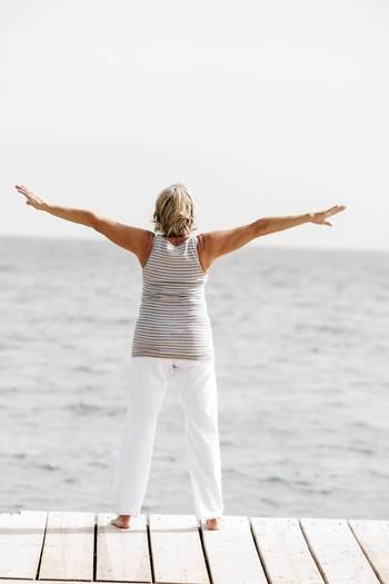Senior woman exercising on dock at water