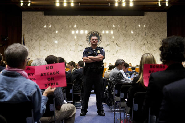 "A Capitol Hill police officer watches as protesters hold signs reading ""No Attack on Syria"" during the Senate Foreign Relations Committee hearing on Syria on Capitol Hill in Washington."