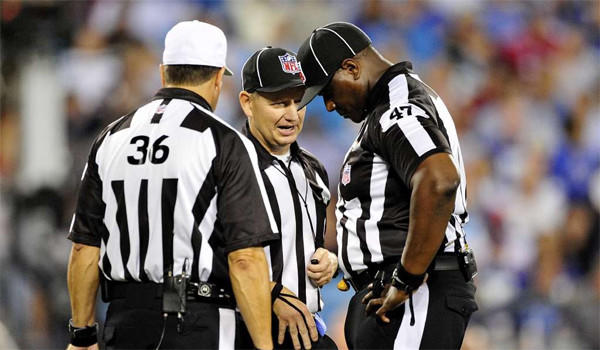 Referees Robert Frazer, left, John Vachon, center, and Lemuel Hawkins, right, confer after throwing a penalty flag during a New York Giants-Carolina Panthers game on Sept. 23, 2012.