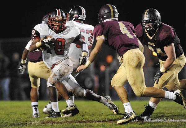 Easton's Shane Simpson (left) looks for room to run past Whitehall's Ryan Bonshak (right) during their Lehigh Valley Conference high school football game Friday October 26, 2012.