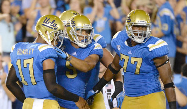 Jordan Payton, center, Brett Hundley, left, and Torian White, right, celebrate after a touchdown during UCLA's 58-20 victory over Nevada.