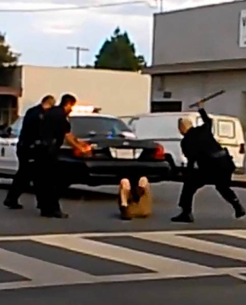 Frame of a video showing Long Beach police officers striking a suspect with a baton. The video can be seen online at bit.ly/14pwsfa. The police chief has vowed a thorough investigation.