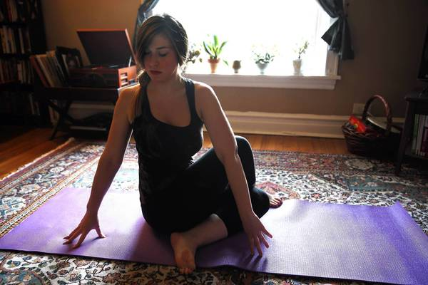 Josie Berg-Hammond, 24, suffered an ACL tear when she was 11, and corrective surgery was delayed for two years because she was still growing. Berg-Hammond, who says her knee still hurts every day, does yoga in her Logan Square apartment in Chicago on Aug. 14.