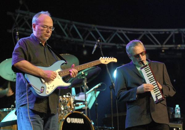 Walter Becker and Donald Fagen (playing melodica) performing live onstage.