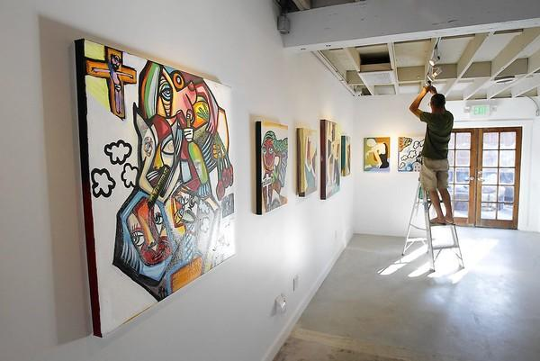 Co-founder Mark Weiner points new lights toward the work by Ben Brough, left, and Katherine Langlands as he prepares for Saturday's opening of the Artist's Republic 4 Tomorrow gallery space, formerly known as ART4T Gallery.