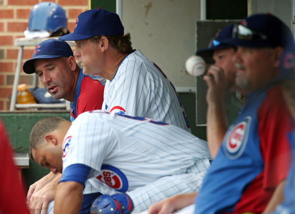 Cubs manager Dale Sveum confers with coaches and players in the dugout in the first inning against the Brewers at Wrigley Field on July 30.
