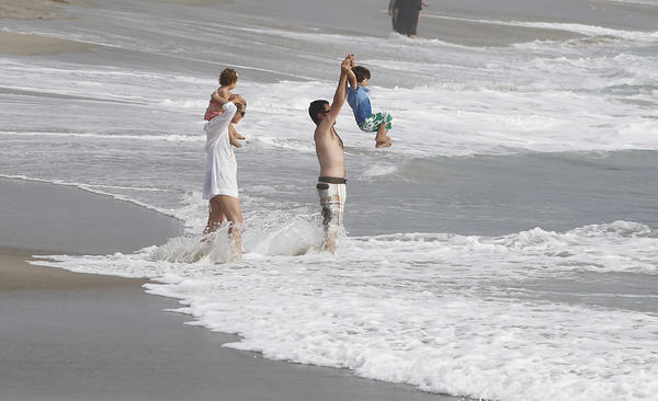 A family enjoys the water and waves during Labor Day at Victoria Beach.