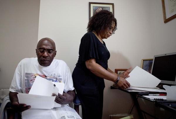 Michael and Patricia Jackson sift through bank documents at their home in Marietta, Ga. The Jacksons struggled to keep a house worth $100,000 less than they owed.