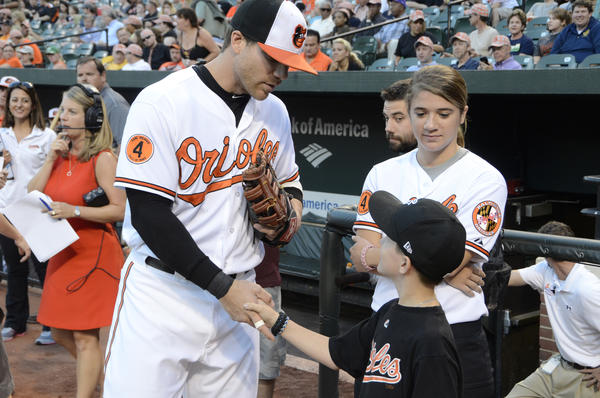 Chris Davis autographs a ball for the son of slain Baltimore County police officer Jason Schneider, Brandon, 10.