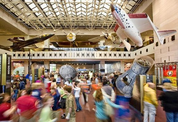 Visitors to the Smithsonian's National Air and Space Museum pass under historic aircraft.